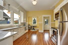 yellow kitchen walls white cabinets kitchen interior with white cabinets yellow walls and wood floor 121787366