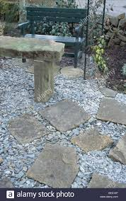 rustic stone table and metal bench on gravel patio with stone