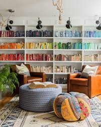 comfy library chairs bookshelves organized by color rainbow colored books with white