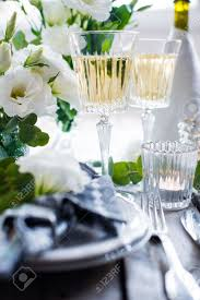 table setting with white flowers candles and glasses of champagne
