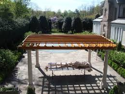 exterior wooden pergola roof covering patio with four white pole