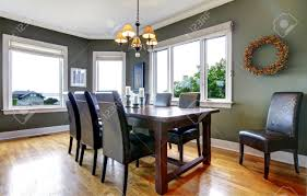 large green dining room with leather chairs and large windows