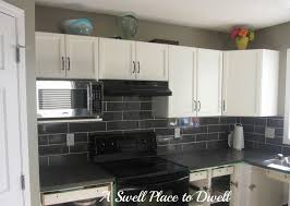 white l shaped cabinetry with granite countertop with grey subway