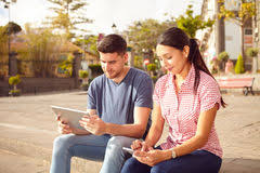 Bench Couple Shirt - young couple sitting in a town square stock photo image 73609440