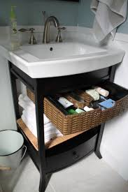 brown rattan basket storage inside black wooden vanity with drawer