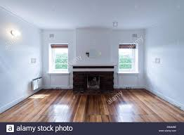 a living room and fireplace above polished floorboards in an empty