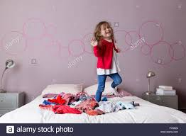 little dancing on a pile of laundry on her parents u0027 bed stock