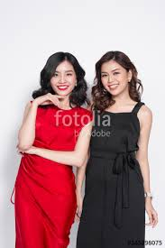 two fashionable women in nice dresses standing together and having