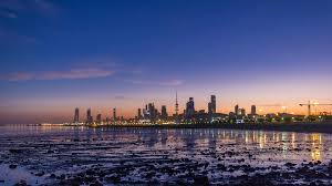 seaside skyline of kuwait city from night to day transition