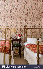 twin wrought iron beds in bedroom with floral patterned wallpaper