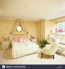 coronet with cream drapes above brass bed with lace bed cover in