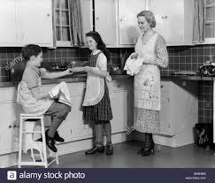 1930s mother daughter son in kitchen washing drying dishes stock