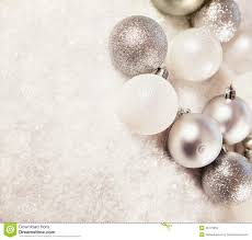 silver and white baubles on snowy background stock photo image