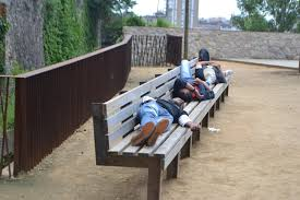 homeless sleeping on a bench flying high solo