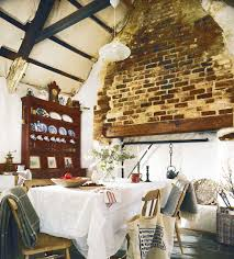 thatched cottage white dining room with exposed brick wall