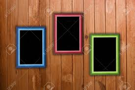 three colorful frames hanging on wooden wall stock photo picture