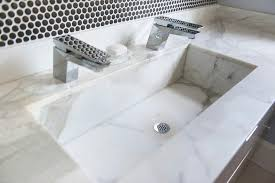 white marble trough sink with two faucets contemporary bathroom