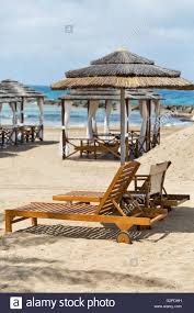 wooden sunbeds and straw umbrella in front of beautiful bungalows