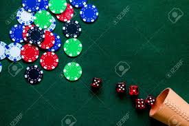 poker table top and chips poker chips and dice on a green gaming table top view stock photo
