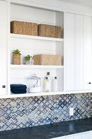 white panel laundry room cabinets with blue mosaic tiles