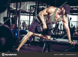 one arm dumbbell rows in gym u2014 stock photo ozimicians 132342960