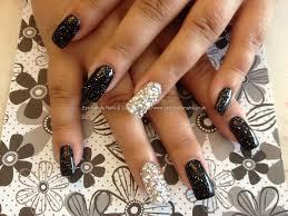 acrylic nails with black glitter polish and swarovski crystals on