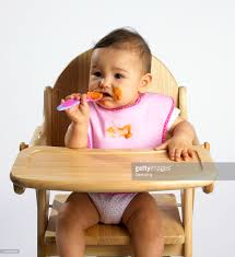 High Sitting Chair Baby Sitting In High Chair With Spoon In One Hand And Food