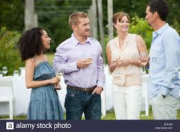 people socialising at outdoor dinner party stock photo royalty