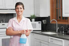 hispanic maid cleaning kitchen stock photo dissolve
