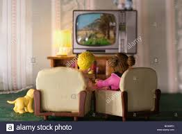 plastic couple watching tv in miniature living room rear view