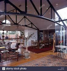 metal girders on roof in open plan house with view of dining and metal girders on roof in open plan house with view of dining and sitting areas