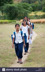 indian girls walking to through the indian countryside