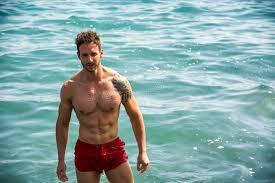 bureau d ude eau homme musculaire se tenant dans l eau d océan sans chemise photo