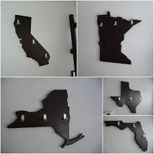 three sheet metal coat hook on unshaped dark brown wooden wall