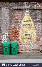 a old red brick wall mural painted with a huge broom with words a old red brick wall mural painted with a huge broom with words sweep leaves not