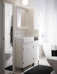 bathroom furniture featuring white arched over the toilet