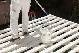 house painter wearing protection spray painting a deck