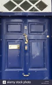 blue front door with polished brass ironmongery stock photo