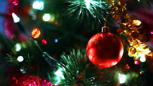 glass toy red ball hangs on christmas tree among of blinking