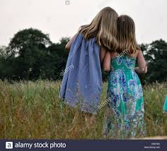 two pretty little girls with blonde hair and summer dresses put