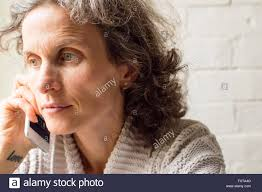 looking with grey hair middle aged woman with grey hair looking thoughtful and using