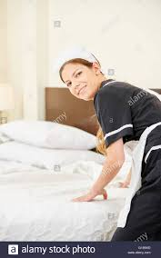 Bed Making Maid In Uniform Cleaning Hotel Room And Making Bed During Stock