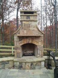 outdoor stone fireplace with hearth and seating wall fireplaces