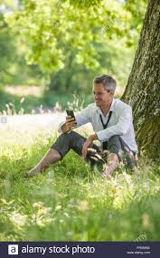 looking with grey hair a nice looking grey hair business man is sitting against a tree in