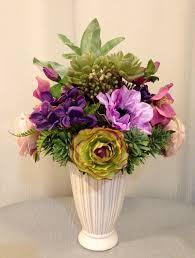 rose anemone ranunculus and succulent plant arrangement in