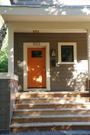 exterior orange wooden front door design ideas with white house