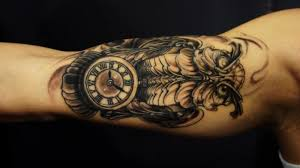 brilliant biomechanical owl and tiny clock for bicep