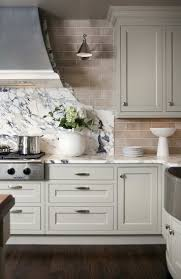 articles with light gray kitchen cabinets with black appliances