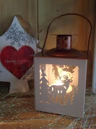 and copper metal christmas lantern with reindeer cut out design