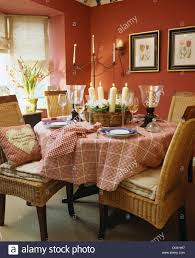 wicker chairs at table set for lunch with red checked cloth and